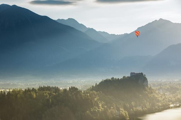 Balão de ar quente que flutua sobre as montanhas. paisagem, vista alpina.