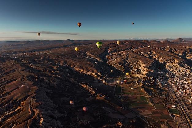 Balão de ar quente que voa sobre a paisagem da rocha em cappadocia turquia.