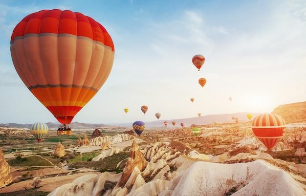Balão de ar quente que voa sobre a paisagem da rocha na turquia. capadócia