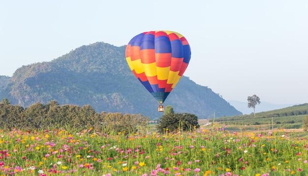 Balão de ar quente sobre campos de flores com fundo de montanha