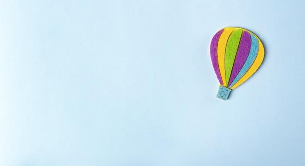 Balão de ar quente sobre fundo azul pastel com espaço de cópia de texto.
