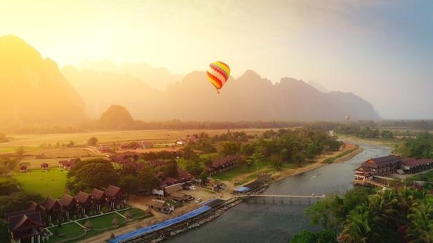 Balão de ar quente sobre o rio nam song em vang vieng, laos no pôr do sol