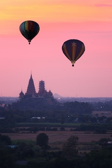 Balão de ar quente voando sobre wat tham sua (templo da caverna do tigre) em kanchanaburi, tailândia