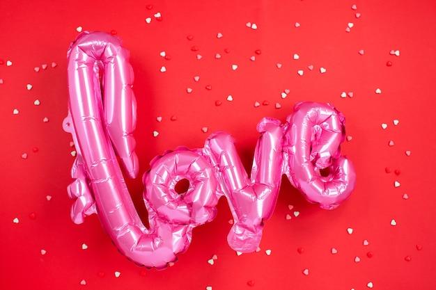 Balão de ar rosa com a forma da palavra amor