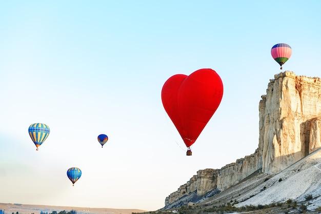 Balão de ar vermelho em forma de coração voando no céu claro