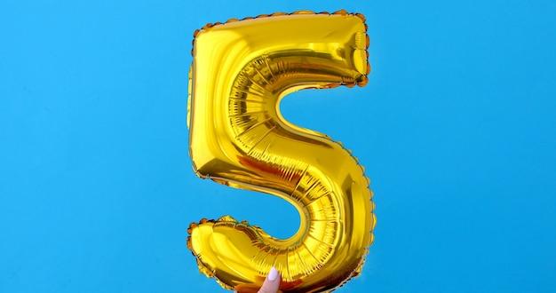 Balão de celebração número 5 da folha de ouro em um azul