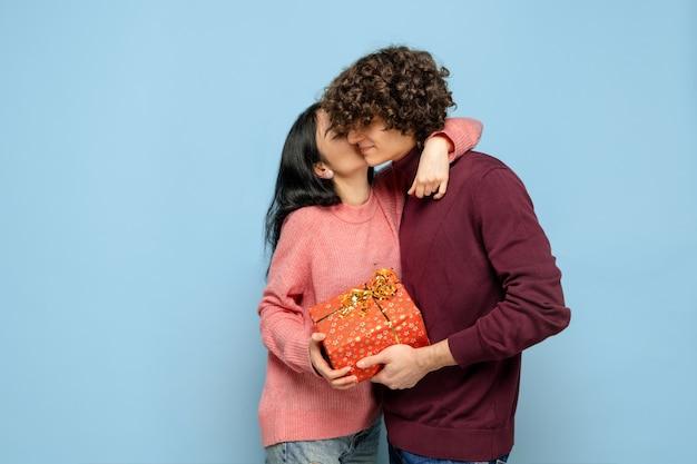 Balão de coração, abraçando. lindo casal apaixonado em fundo azul do estúdio. dia de são valentim, amor, relacionamento e conceito de emoções humanas. copyspace. jovem e mulher parecem felizes juntos.
