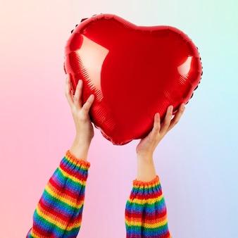 Balão de coração da comunidade lgbtq + segurado pelas mãos