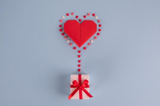 Balão de coração de papel origami com caixa de presente na mesa azul