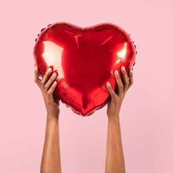 Balão de coração para dia dos namorados segurado por uma pessoa