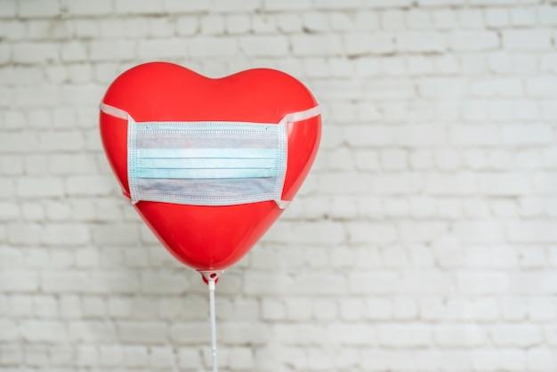 Balão de coração vermelho em máscara médica no fundo da parede de tijolos brancos, dia dos namorados durante o conceito de pandemia