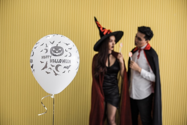 Balão de halloween branco no fundo jovem casal fantasiado de bruxa e drácula e segurar o pirulito na parede amarela do conceito de halloween.