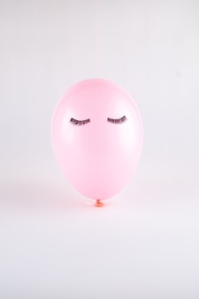 Balão de rosto rosa com cílios pretos olhos fechados. conceito mínimo