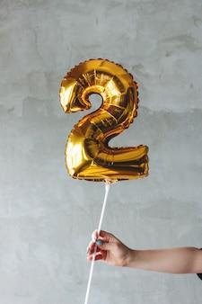 Balão do número dois do ouro em uma mão fêmea na parede cinzenta isolada