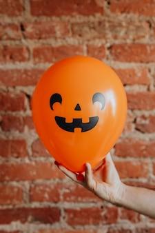 Balão laranja de halloween em uma mão