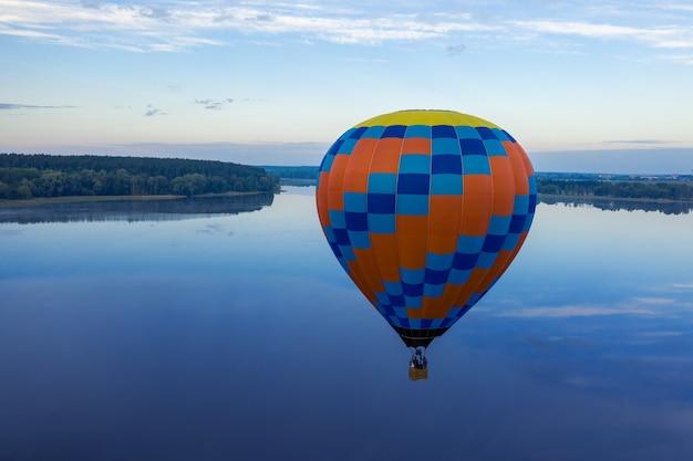 Balão sobre o lago, vista do drone. balão amarelo e azul em um fundo de madrugada.
