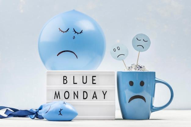 Balão triste e caneca com caixa de luz para segunda-feira azul