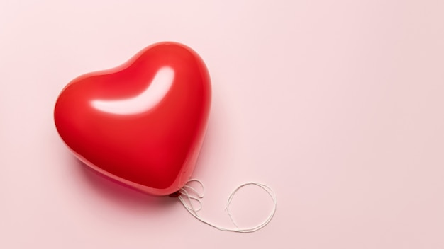 Balão vermelho em forma de coração em fundo rosa pálido. conceito de dia dos namorados.
