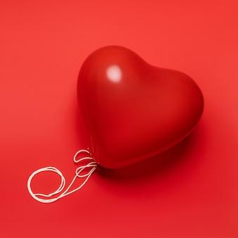 Balão vermelho em forma de coração em fundo vermelho pálido. conceito de dia dos namorados.