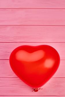 Balão vermelho em fundo de madeira.