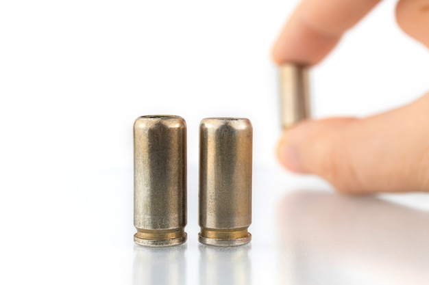 Balas de 9 mm isoladas em um fundo branco, mão com projétil