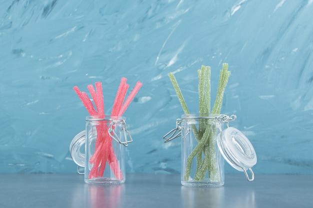 Balas de gelatina azeda em recipientes de vidro.