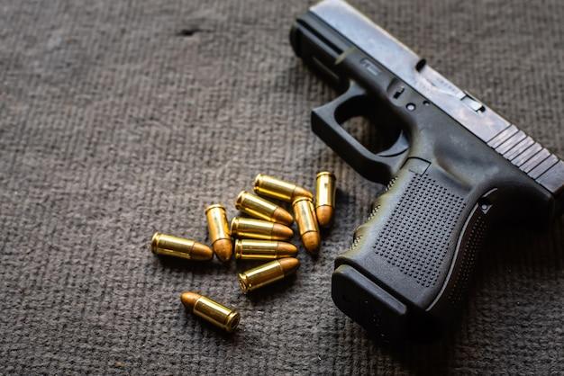 Balas e arma na mesa de veludo preto