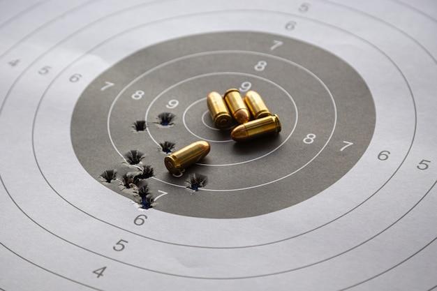 Balas no alvo de papel para a prática de tiro