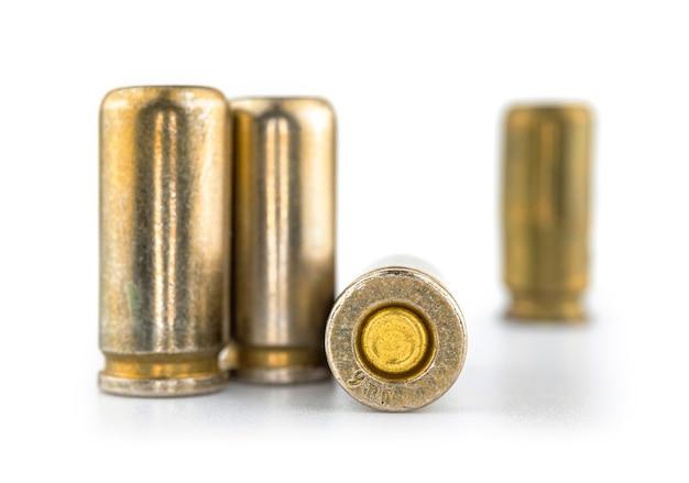 Balas para arma isoladas em fundo branco com reflexo, cartuchos para pistola 9mm, foto ilustrativa