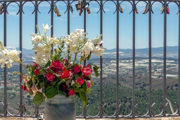 Balaustrada com vaso de lírios lilium candidum e rosas chimensis e cadeados colocados pelos amantes