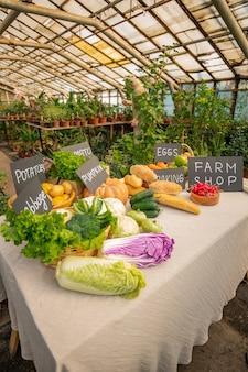 Balcão cheio de vegetais frescos com etiquetas no mercado de fazendeiros, conceito de colheita