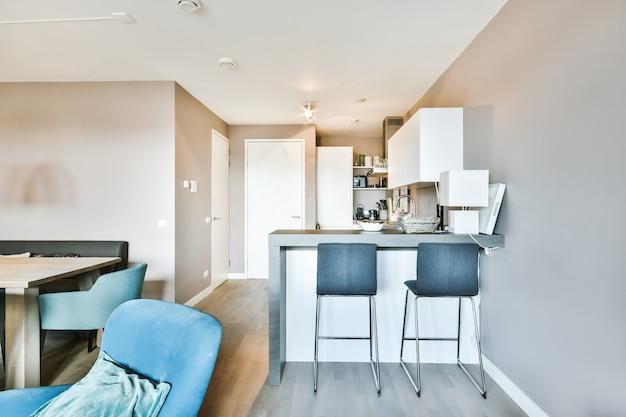 Balcão com cadeiras dividindo cozinha com móveis modernos da área de jantar em apartamento contemporâneo