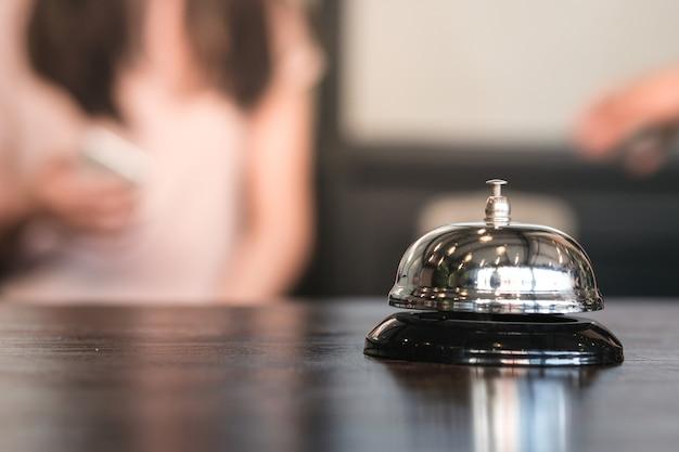 Balcão da recepção do hotel com campainha de serviço.