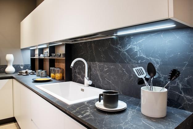 Balcão de cozinha de efeito mármore com utensílios