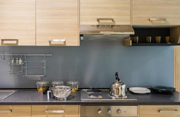 Balcão de cozinha moderno com acabamento em madeira dura e bancada em granito e armário de madeira
