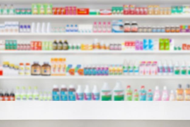 Balcão de madeira vazio com prateleiras de farmácias desfocam o fundo de produtos farmacêuticos