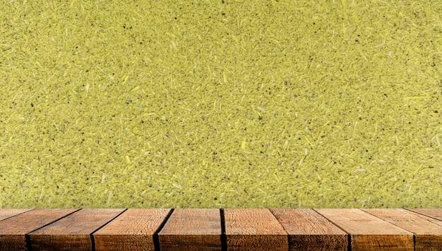 Balcão de mesa de prateleira de placa de exposição de madeira com espaço de cópia para o pano de fundo de publicidade e fundo com fundo de parede de madeira compensada amarela.