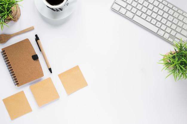 Balcão de negócios branco com diário; notas adesivas; xícara de café e teclado na mesa branca
