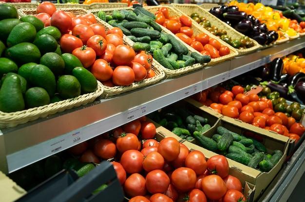 Balcão de supermercado com cestas de vime e caixas de talão com tomates, pepinos e abacates