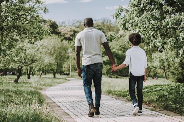 Balck pai segurando a mão do seu filho e caminhando juntos.