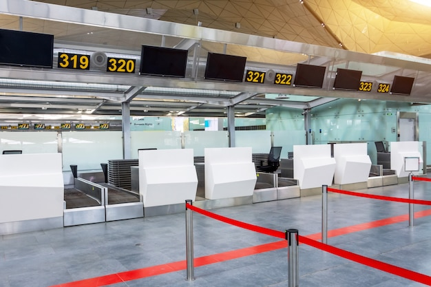 Balcões de check-in vazios para entrega de bagagem com caminhos cancelados com uma fita vermelha para diferenciar passageiros no terminal do aeroporto.