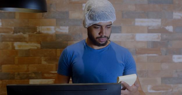 Balconista com um boné na cabeça anotando o pedido de uma cliente. pessoas latinas