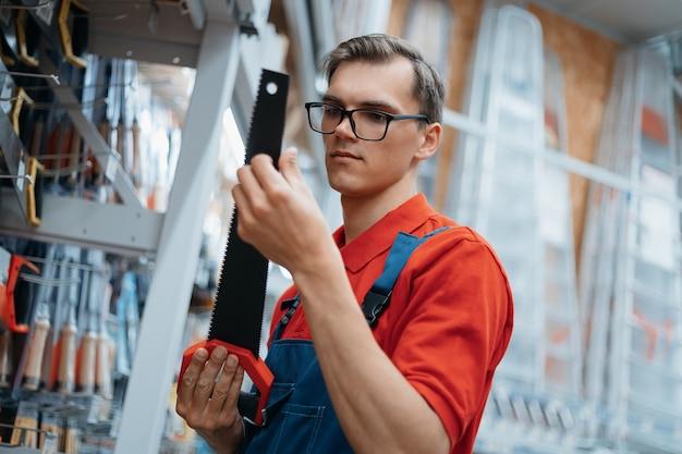 Balconista de loja de ferragens verificando as marcações em uma serra manual