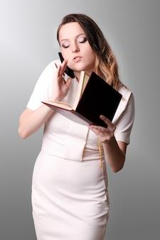 Balconista fêmea bonita que está no escritório em seu local de trabalho, segurando o planejador, lendo o calendário para o dia, retrato da vista lateral