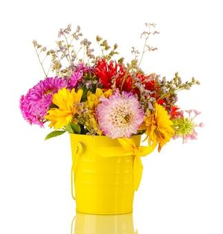Balde amarelo brilhante com flores isoladas em branco
