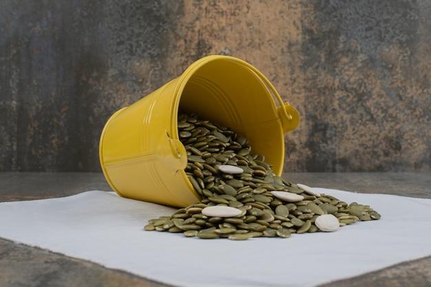 Balde amarelo cheio de sementes descascadas de abóbora na toalha de mesa branca.