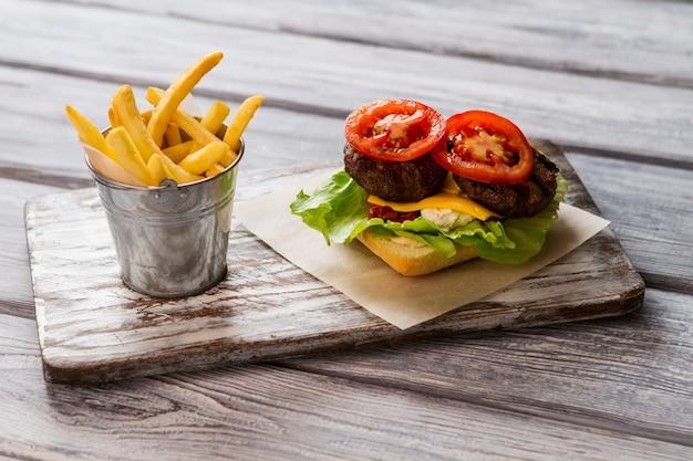 Balde cheio de batatas fritas. fatia de tomate e carne grelhada. ingredientes para um hambúrguer saboroso. você deve provar isso.