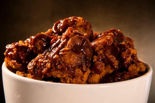 Balde cheio de frango frito kentucky crocante com fumaça e molho de churrasco no fundo marrom. foco seletivo.