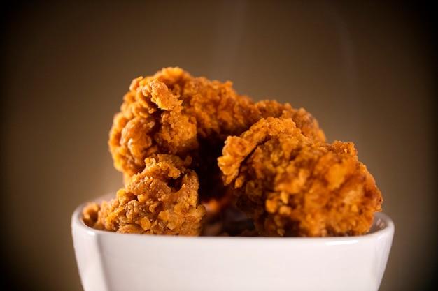 Balde cheio de frango frito kentucky crocante com fumaça no fundo marrom. foco seletivo.