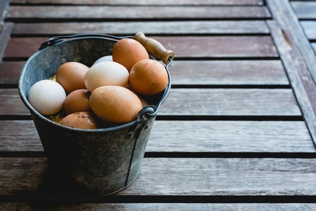 Balde cheio de ovos de galinha branca e marrom.